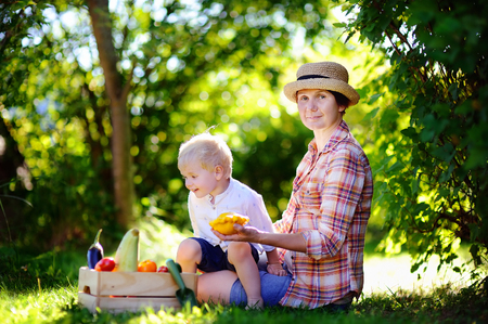 Beautiful middle aged women and her adorable little grandson enjoying harvest. Healthy family lifestyle photo