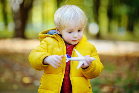 Cute toddler boy playing with toy airplane in a autumn park. Outdoors child leisure. Game for little kid