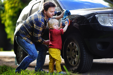 Middle age father with his toddler son washing car together outdoors. Family together activity