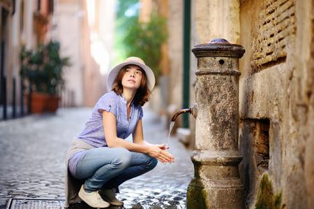 若い女性が市の泉で手を洗います。Rome, イタリアの噴水からきれいな水を飲む若い女性