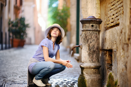Young woman washing hands in a city fountain. Young woman drinking clean water from the fountain in Rome, Italy