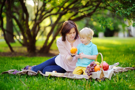 babysit: Beautiful little boy with his young mother having a picnic in summer sunny park. Outdoors leisure time for kids or family. Cute child eating grapes