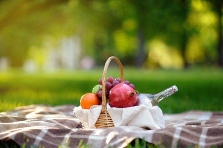Picnic basket with fruits, food and water in the glass bottle. Outdoors leisure time for kids, family or dating couple. Sunny warm day in the summer park.