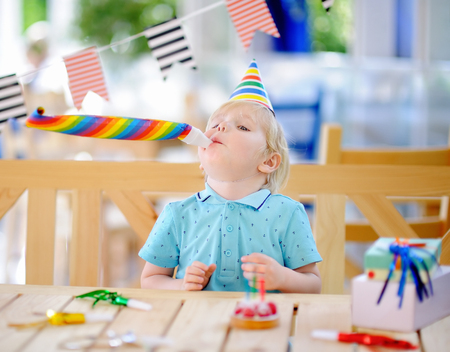 Cute little boy celebrate birthday party with colorful decoration and cake. Child with sweets, candy, whistleblowerhorn and festive gifts. Preschooler or toddler birthday party.