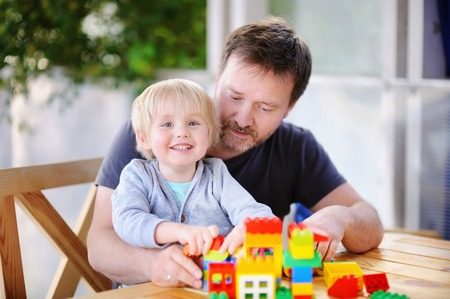 Little boy with his father playing with colorful plastic blocks at home. Development toys for preschooler children Stock Photo