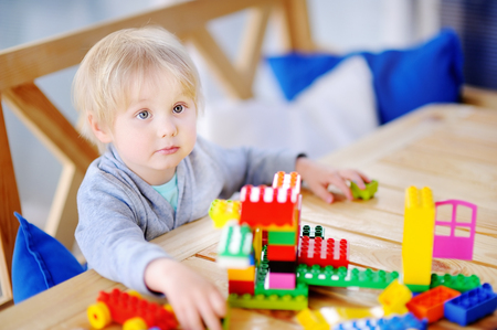 Little boy playing with colorful plastic blocks at kindergarten or at home. Development toys for preschooler children Stock Photo