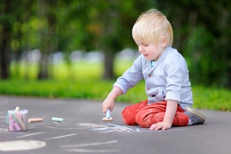 アスファルトの上を色チョークで描く幸せの小さな子供男の子は。夏の公園で幼児子供のための創造的なレジャー。ストリート アートは、子供の教育。 写真素材 - 82915580