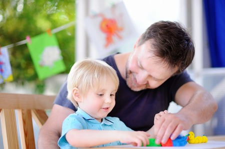 Little boy with his father playing with colorful modeling clay. Little kid molding at home. Development toys for preschooler children Stock Photo