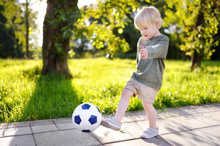 Kleine jongen met plezier met een voetbalwedstrijd op zonnige zomerdag. Actief buitenspel spel voor peuter en familie met kinderen
