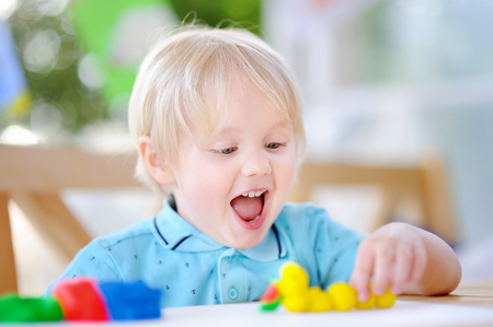Creative boy playing with colorful modeling clay at kindergarten. Little kid molding at home. Development toys for preschooler children