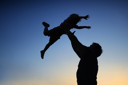 Loving father and his little son having fan together outdoors. Happy family. Fatherhood. Toddler boy and his dad playing. Family as silhouette on sunset. photo