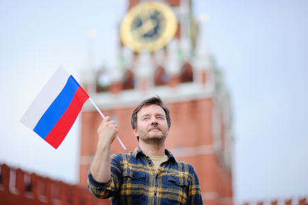 Middle age man with russian flag with Spasskaya tower (Russia, Moscow) on background. Patriotic feelingpatriotism concept