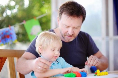 Little boy with his father playing with colorful modeling clay. Little kid molding at home. Development toys for preschooler children photo