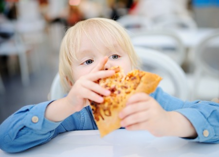Cute blonde boy eating slice of pizza at fast food restaurant. Child unhealthy meal concept