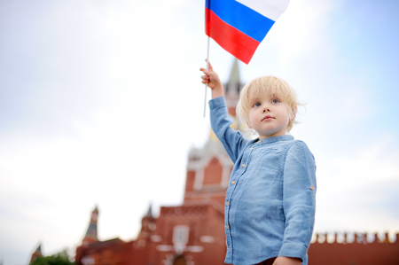 Cute little boy with russian flag with Spasskaya tower (Russia, Moscow) on background. Patriotic feelingpatriotism concept
