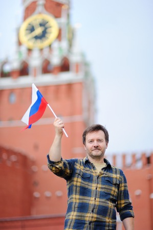 Middle age man with russian flag with Spasskaya tower (Russia, Moscow) on background. Patriotic feeling/patriotism concept photo
