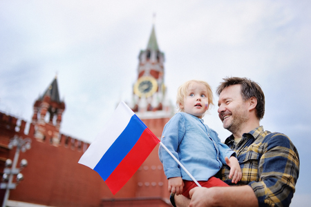 Middle age man and his little son with russian flag with Spasskaya tower (Russia, Moscow) on background. Patriotic feeling/patriotism concept photo