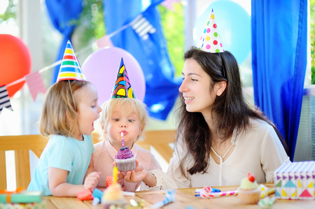 Little child and their mother celebrate birthday party with colorful decoration and cakes with colorful decoration and cake. Family with sweets, candy, whistleblowerhorn and festive gifts. Boy and girl birthday party.