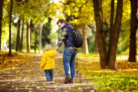 Father and his toddler son walking in autumn forest. Family outdoor leisure in park. photo