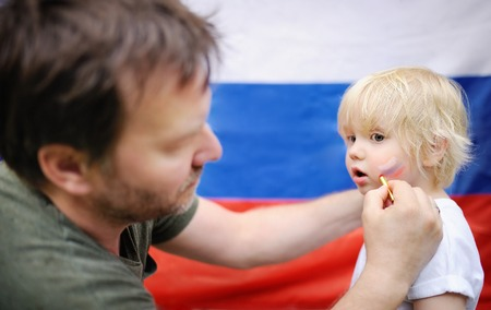 Man drawing russian flag on cheek of his little son. Fans family supporting and cheering their national team with russian flag on background photo