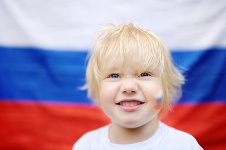 Portrait of cute little boy with russian flag on background. Fans child supporting and cheering their national team