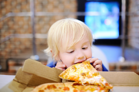 Cute blonde boy eating slice of pizza at fast food restaurant. Child unhealthy meal concept. Hungry kid. Pizza recipe. Stock Photo