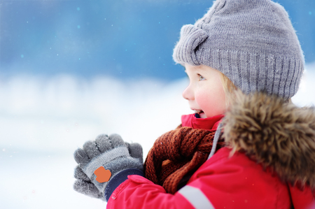 Little boy in red winter clothes having fun with snow. Active outdoors leisure with children in winter. Kid with warm hat, hand gloves and scarf