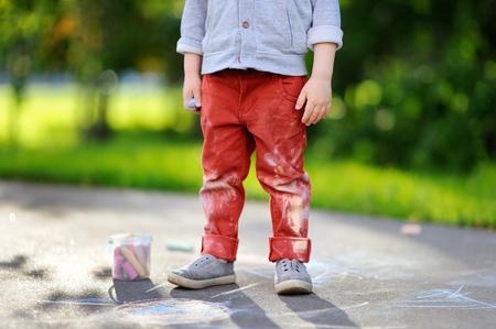 Close-upfoto van de kleine tekening van de jong geitjejongen met gekleurd krijt op asfalt. Creatieve vrije tijd voor peuterkind in de zomerpark. Straatkunst, kinderopvoeding. Vuile kleding.