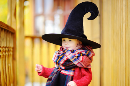 Toddler boy in pointed hat playing outdoors. Little wizard Stock Photo