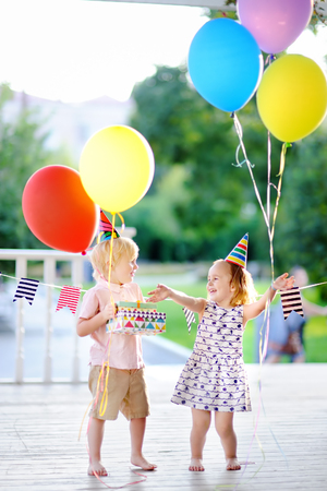 Little boy and girl having fun and celebrate birthday party with colorful balloons. Happy child with festive gifts. Preschoolers or toddlers birthday party in summer park 免版税图像