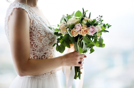 Bride holding stylish wedding flowers. Elegance rustic style pastel colors bouquet in woman hands Stock Photo