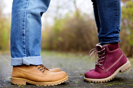 Closeup photo of male and female legs during a date in autumn park. Love, couple, romantic concept