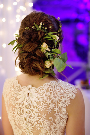 Beauty wedding hairstyle with natural flowers for young bride. Stylish wedding look