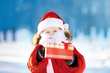 Funny little boy wearing Santa Claus costume with gift box in winter snowy park. Toddler child waiting Christmas Stock Photo
