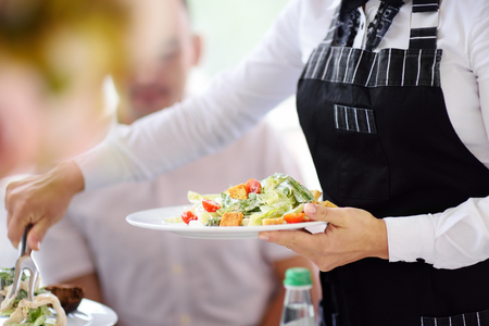 Waiter carrying plates with salad on some festive event, party or wedding reception