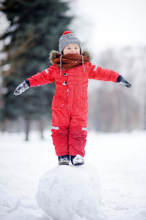 Little boy in red winter clothes having fun with snowball. Active outdoors leisure with children in winter. Kid during stroll in a snowy winter park Imagens