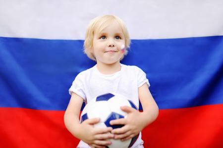 Portrait de l'adorable petit garçon avec un drapeau russe sur fond. Fans enfant soutenant et encourageant leur équipe nationale lors des matchs de football / football