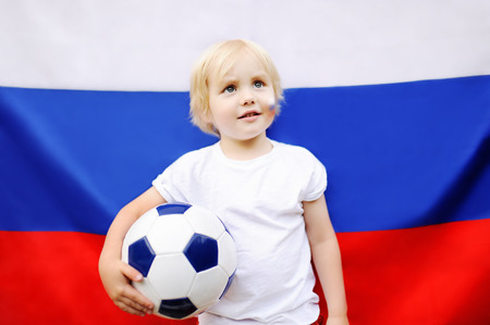 Portrait of cute little boy with russian flag on background. Fans child supporting and cheering their national team at the soccerfootball sporting games