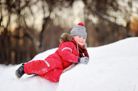 Little boy in red winter clothes having fun with fresh snow. Active outdoors leisure with children in winter. Kid during stroll in a snowy winter park