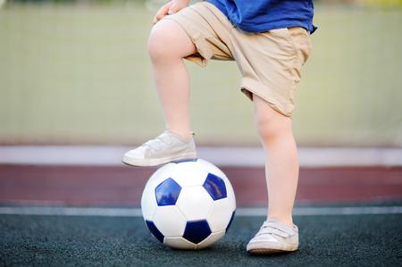夏の日にサッカーフットボールの試合を楽しんでいる小さな男の子。子供のためのアクティブな屋外ゲームスポーツ。キッズサッカークラスとキャ