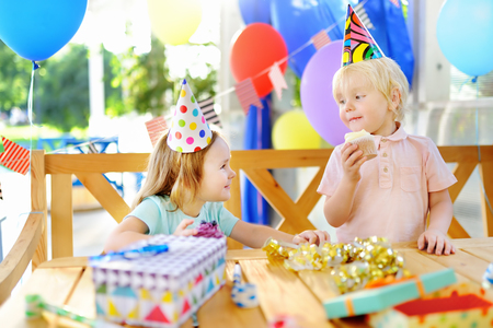 Little boy and girl having fun and celebrate birthday party with colorful decoration and cake. Child with sweets, candy, whistleblowerhorn and festive gifts. Preschoolers or toddlers birthday party.