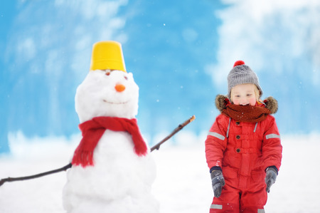 Little boy in red winter clothes having fun with snowman. Active outdoors leisure with children in winter. Kid during stroll in a snowy winter park