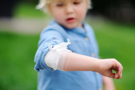 Cute little boy looking on his elbow with applied bandage. Child healthcare and medicine concept. First aid.