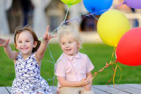 Little boy and girl having fun and celebrate birthday party with colorful balloons. Happy child with festive gifts. Preschoolers or toddlers birthday party in summer park Фото со стока