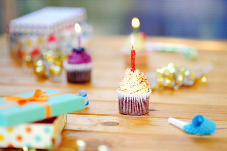 Birthday party with colorful decoration and cakes with candles. Closeup photo with sweets, confetti, candy, whistleblowerhorn and festive gifts.