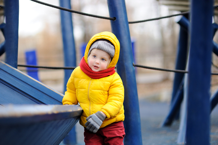 Cute little boy having fun on outdoor playground. Spring, autumn or winter active leisure for kids. Stock Photo
