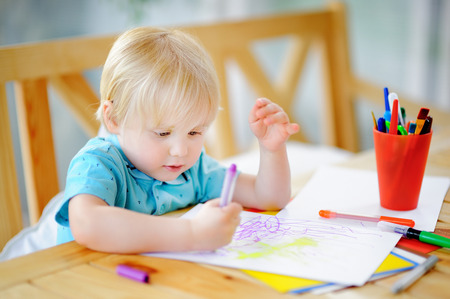 Cute little boy drawing and painting with colorful markers pens at kindergarten. Creative kid painting at playschool. Development toys for preschooler children