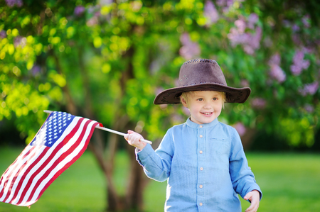 Cute toddler boy holding american flag in beautiful park. Independence Day concept.