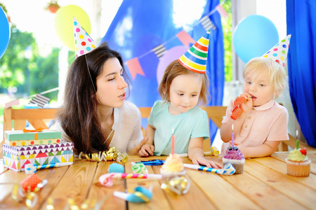 Little child and their mother celebrate birthday party with colorful decoration and cakes with colorful decoration and cake. Family with sweets, candy and festive gifts. Boy and girl birthday party.