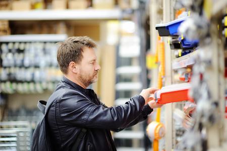 Middle age man choosing the right tool box in a hardware store. DIY concept Reklamní fotografie